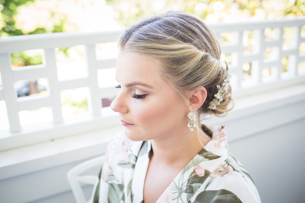 bride with natural bridal makeup and eyeliner, blonde hair twisted into low updo
