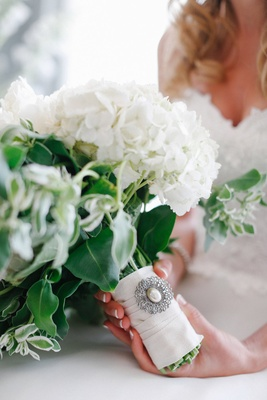 White wedding bouquet with green accents and silver brooch with pearl