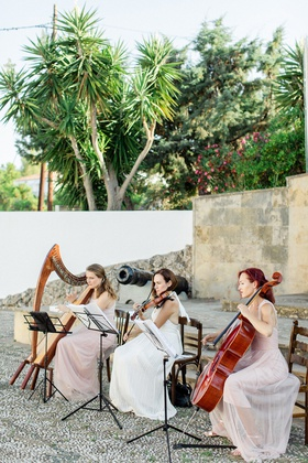 trio of string musicians performing at wedding ceremony, harpists, cellist, violin