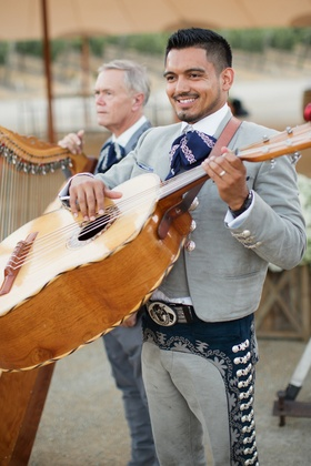 Mexican man in mariachi outfit with big guitar