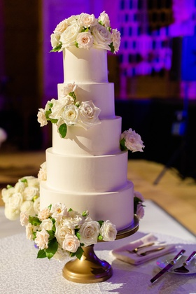 five tier wedding cake with matte frosting and fresh flowers on gold cake stand