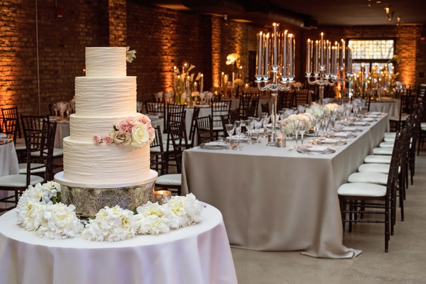 wedding cake with four layers fresh roses flowers pink ivory champagne brick wall venue silver linen