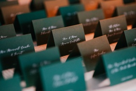 emerald green escort cards with white calligraphy script on table with white linen