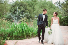 Bride in a strapless Anne Barge ball gown with sweetheart neckline, beaded belt, tulle skirt, groom