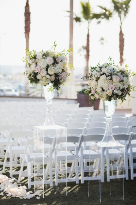 wedding ceremony ocean view white chairs flower petal aisle clear lucite riser pink white flowers