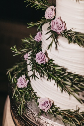 close-up of white wedding cake with tiers decorated with rosemary sprigs and mini lavender roses