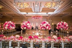 wedding reception ballroom pink flowers gold chairs large dance floor ballroom chandelier