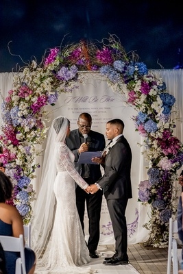 bride and groom exchange vows in front of poem on backdrop arch of blue and purple flowers