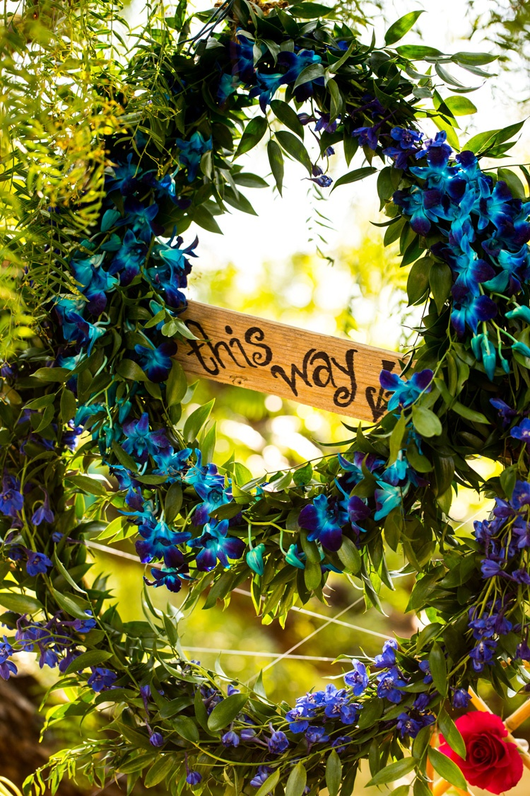 "wreath of dyed blue orchids surround sign reading ""this way"" with arrow, alice in wonderland inspira"