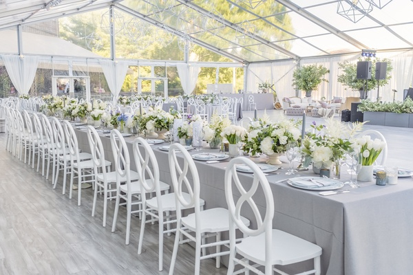 clear-topped tent, grey linens, white round and cross-back chairs