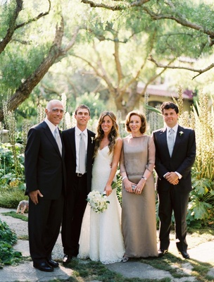 Bride in a Monique Lhuillier gown with groom in black tuxedo and gray tie with family