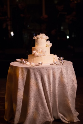 white three tier cake featuring blush flowers surrounded by small candles