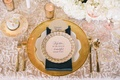 Wedding reception place setting with golden charger, gold rimmed and patterned china, golden flatwar