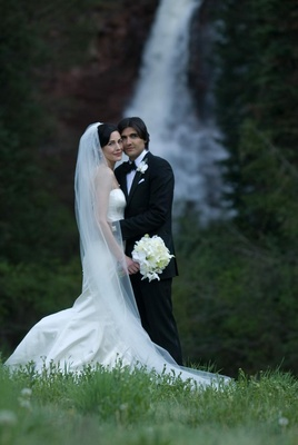 Bride and groom in front of Colorado waterfall