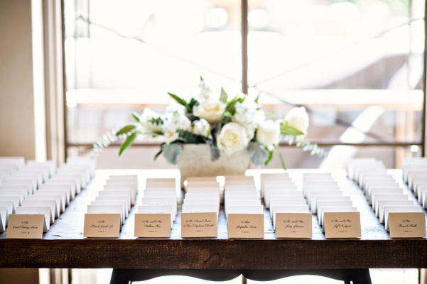Wedding reception escort card table small arrangement of white flowers white place cards wood table