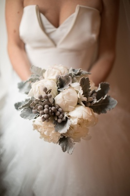 Bride holding white peony with silver brunia balls dusty miller winter wedding bouquet ideas