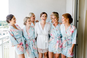 bride in white lace trim silk robe with bridesmaids in matching light blue pink robe flower print