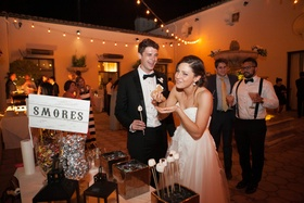 bride and groom eat from the s'mores bar at their wedding