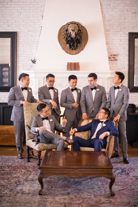 groomsmen in grey in lounge surrounding groom in navy sitting in vintage chair