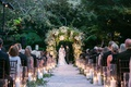 bride and groom under greenery arch hotel bel-air candles lining aisle with greenery