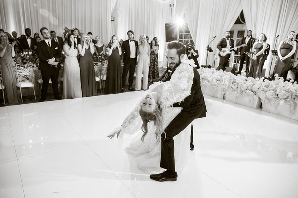 black and white photo of first dance groom dipping bride while guests clap and watch live band