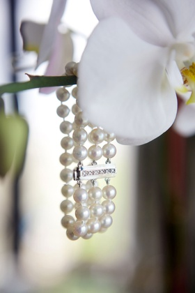 White phalaenopsis orchid with three strand pearl bracelet hanging from it wedding jewelry
