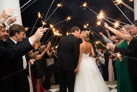 Bride and groom kiss under tunnel of sparklers