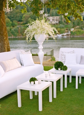 White lounge furniture on grass with view of river