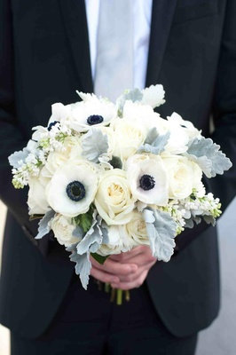 Groom holding dusty miller with ivory rose and white and blue anemone bouquet