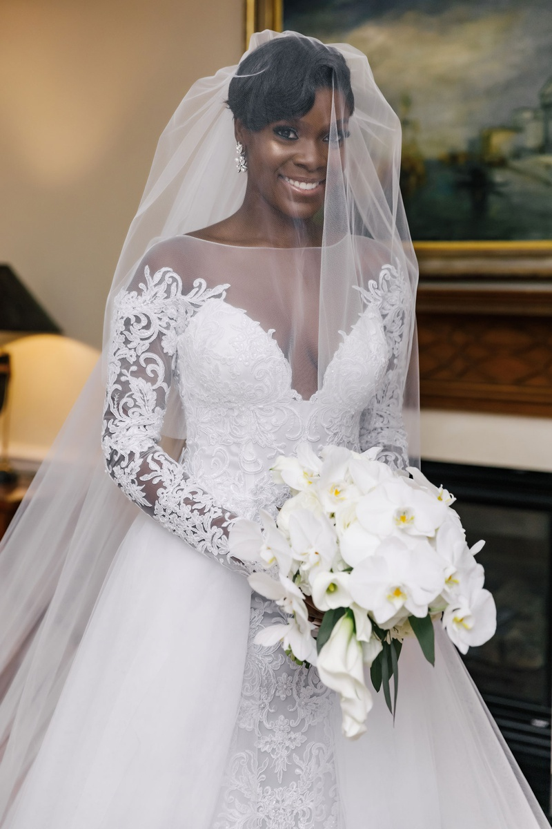 bride in illusion neckline long sleeve a line wedding dress overskirt white orchid bouquet veil