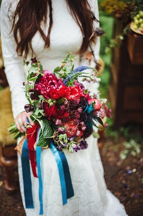 Bride's bouquet of wildflowers in red, purple, blue colors and greenery wrapped with blue ribbons