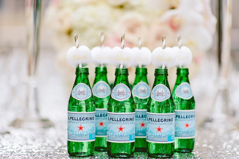 Wedding reception with S.Pellegrino bottles, gold & white straws, Wet Your Whistle labels