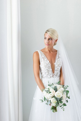 bride in francesca miranda wedding dress with butterfly appliques and plunging neckline