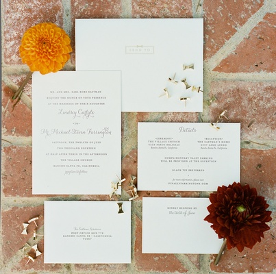 Simple white wedding invitations with wedding information and gold bow pins