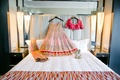 traditional indian bridal dress laid out on bed