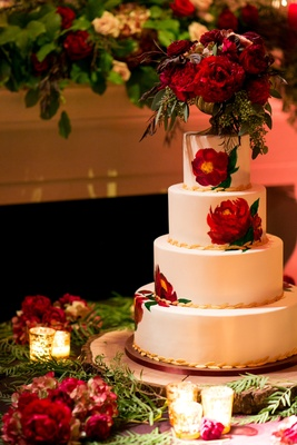 White wedding cake with gold leaf details and painted red peonies with gold footed vase peony topper