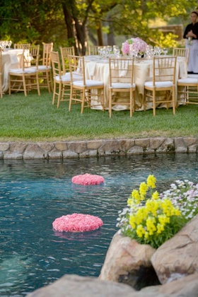 Pink bed of flowers and candles on backyard pool