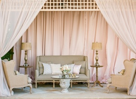 Wedding reception lounge area draped in pink fabric with elegant furniture