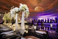 Purple lighting on dance floor and tall centerpieces