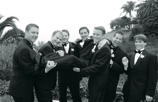 Groomsmen in tuxedos pick up groom