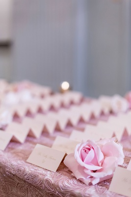 wedding reception ballroom entrance long table textured pink linens and rose with tent escort cards