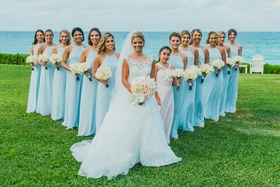bride in isabelle armstrong with bridesmaids in bright blue amsale gowns posed in V forma