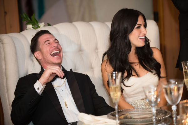 groom laughs during wedding toasts tufted white loveseat furniture