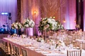 long dinner table with tall centerpieces with branches and flowers and smaller flower arrangements