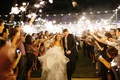 Bride in a strapless Martina Liana dress and groom in black suit run through sparkler send-off
