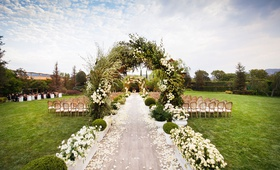 wedding ceremony archway of greenery boxwood white flower boxes wood aisle runner chairs green lawn