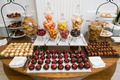 wedding reception dessert table with macarons, truffles, chocolate chip cookies, fruit tarts and mor