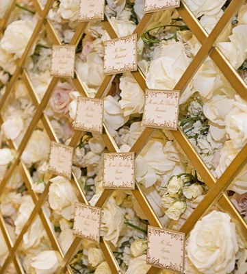 gold printed escort cards on gold trellis backed by wall of flowers
