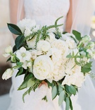 Bride holding bouquet of fresh greenery, white peony and rose flowers romona keveza wedding dress