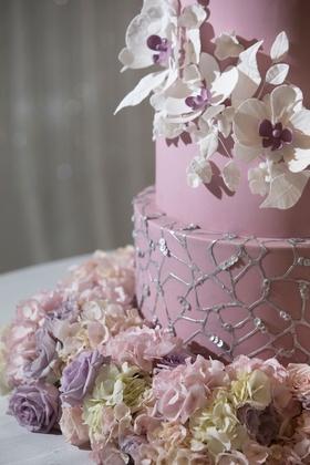 Wedding cake with white sugar flower with purple center fresh flower base silver web design sequins